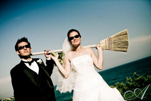 becky-and-danny-wedding-bride and groom with a broom- view of the ocean- destination wedding in Newport RI