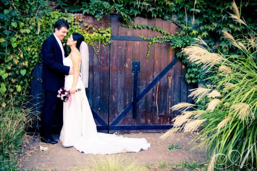 bride and groom in gardens by wine cave at hans fahden winery in calistoga- wine country wedding portraits