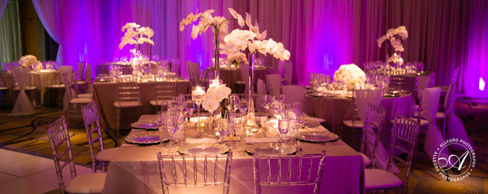 orchids and acrylic chairs with gold chargers and purple lights