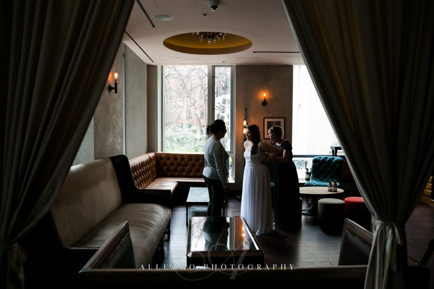 bride puts on dress- hotel nine zero -photo by allegro photography