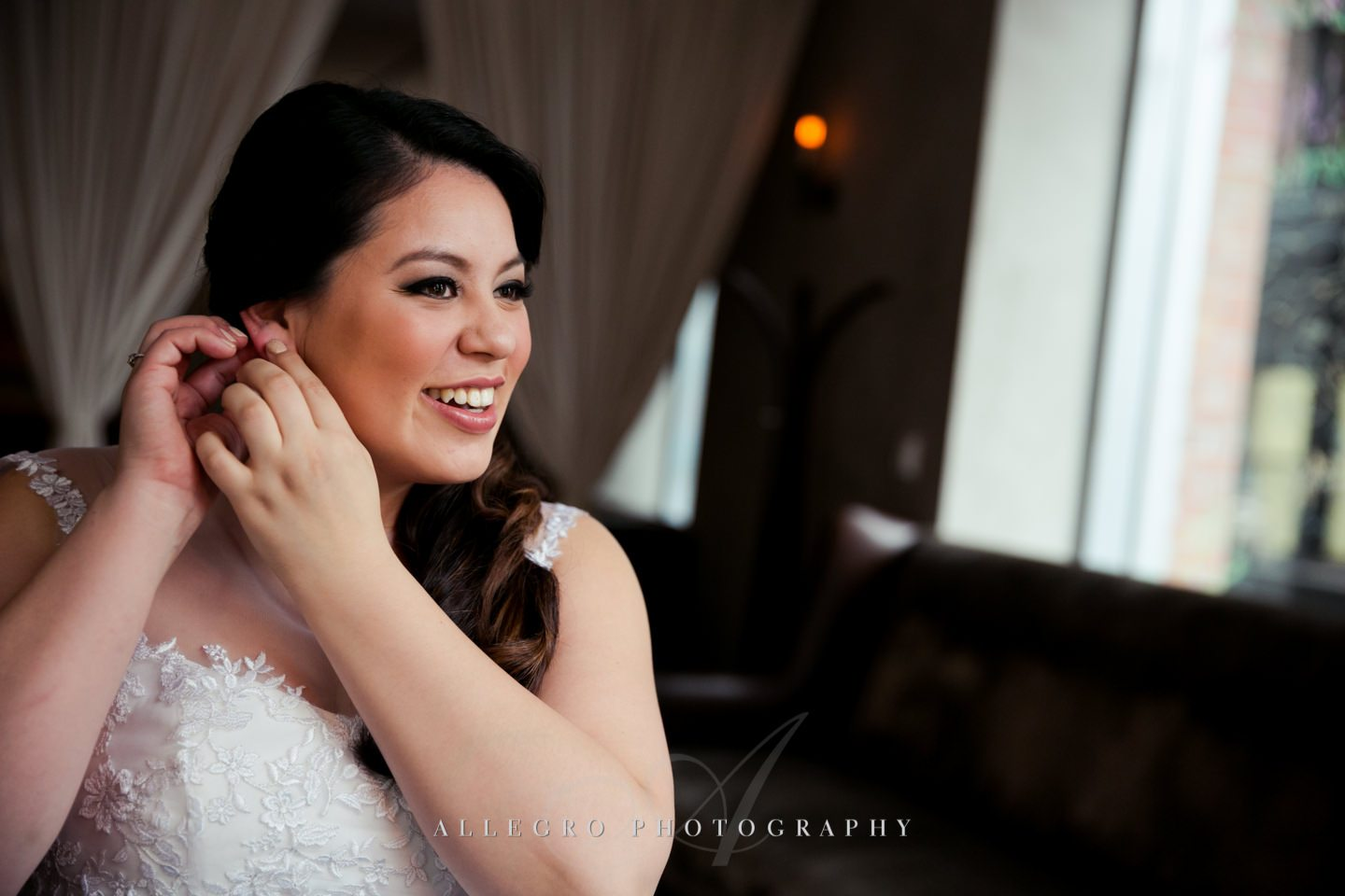 bride puts on wedding jewelry earrings  -photo by allegro photography