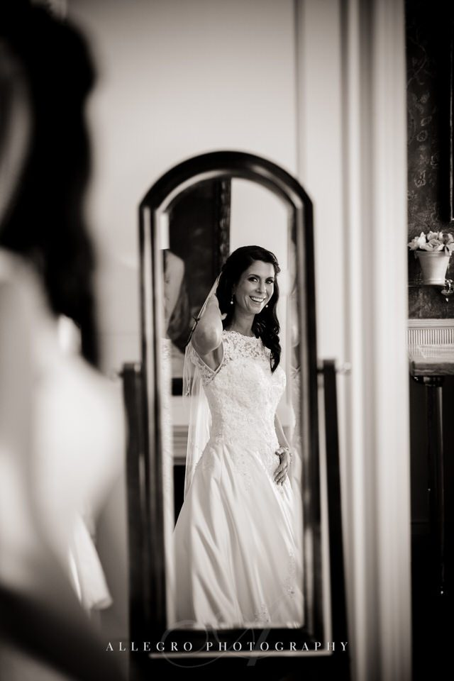 bride checks herself out in mirror - photo by Allegro Photography