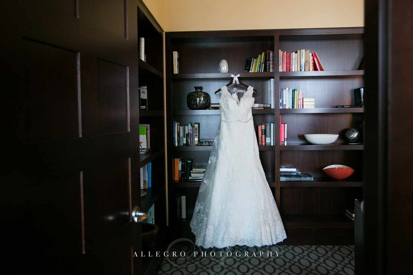 wedding dress hanging on bookshelves