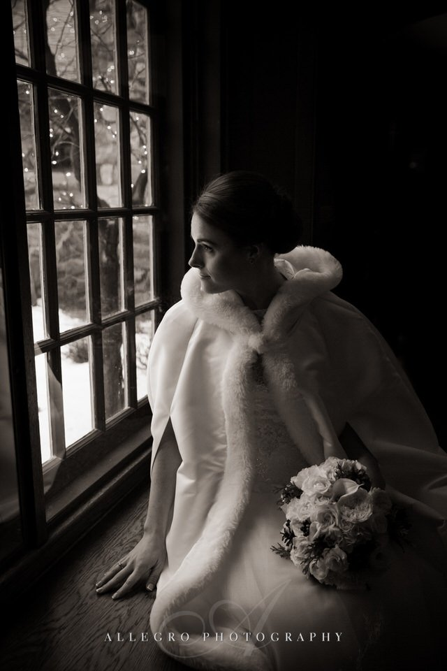fur lined wrap for bride at window- winter wedding willowdale topsfield ma