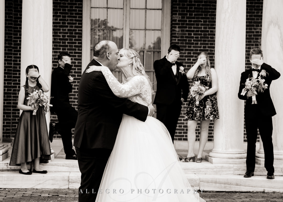 Wedding couple kissing with kids covering their eyes | Allegro Photography