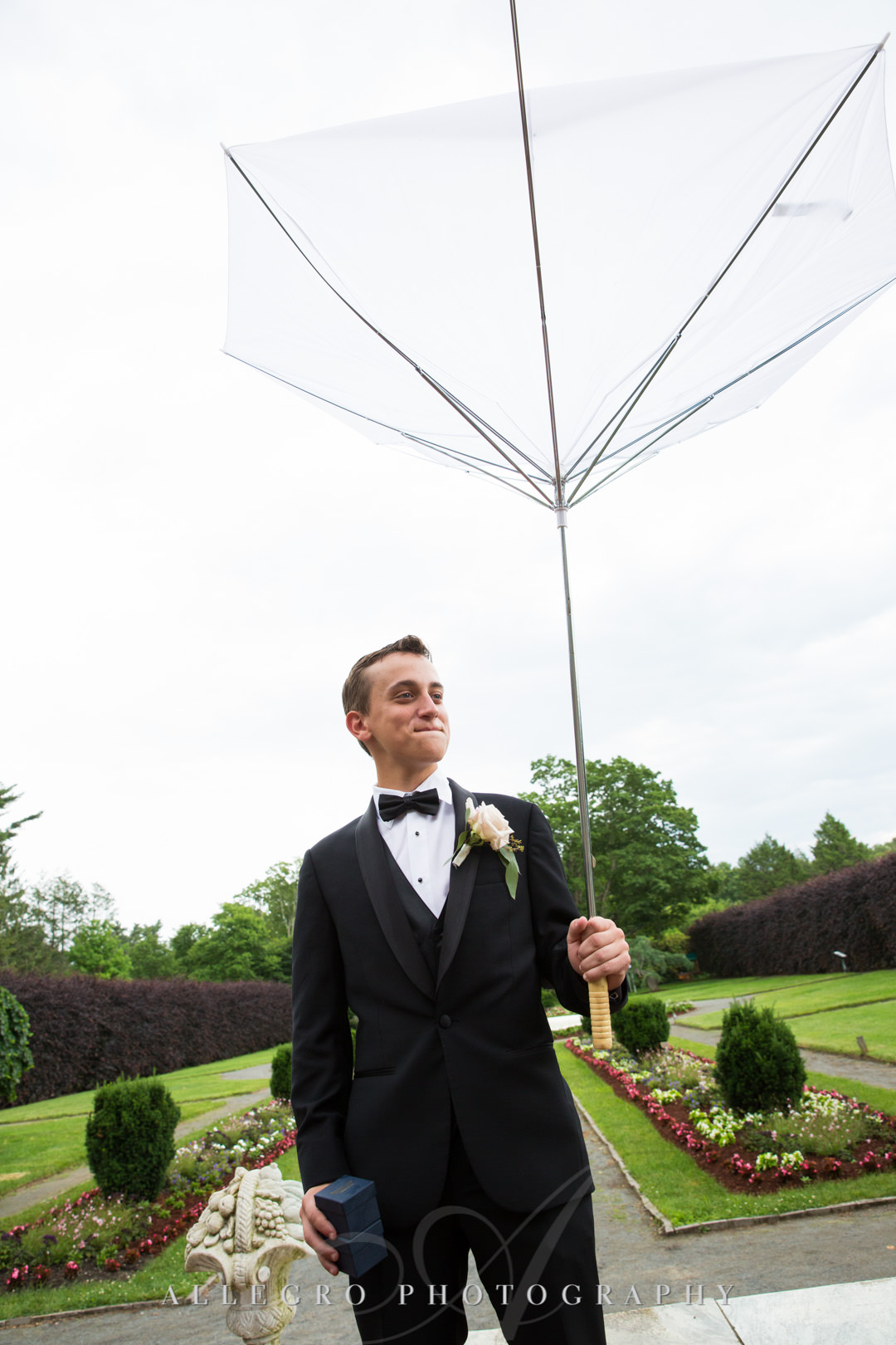 Son of groom holding upside-down umbrella | Allegro Photography