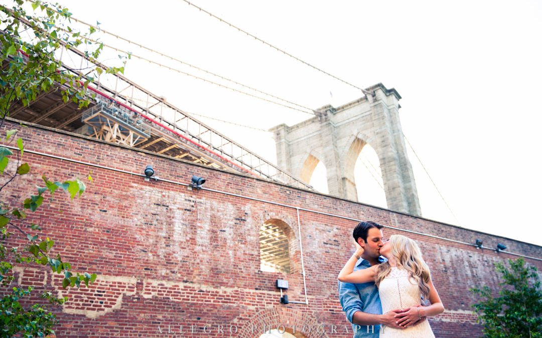 Engaged couple kissing in front of Brooklyn Bridge | Allegro Photography