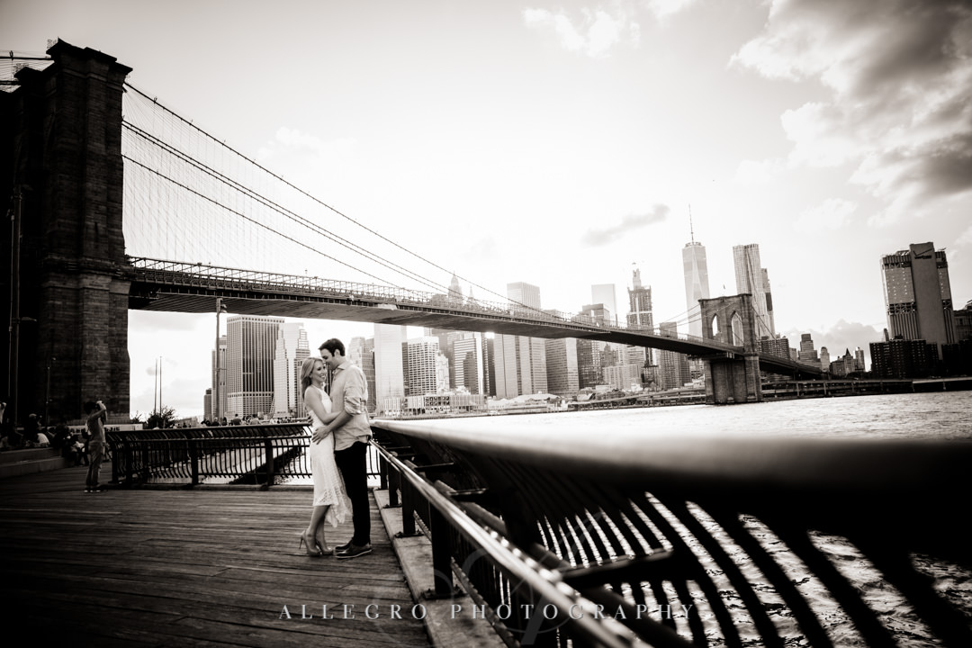 Engaged couple against Brooklyn Bridge skyline | Allegro Photography