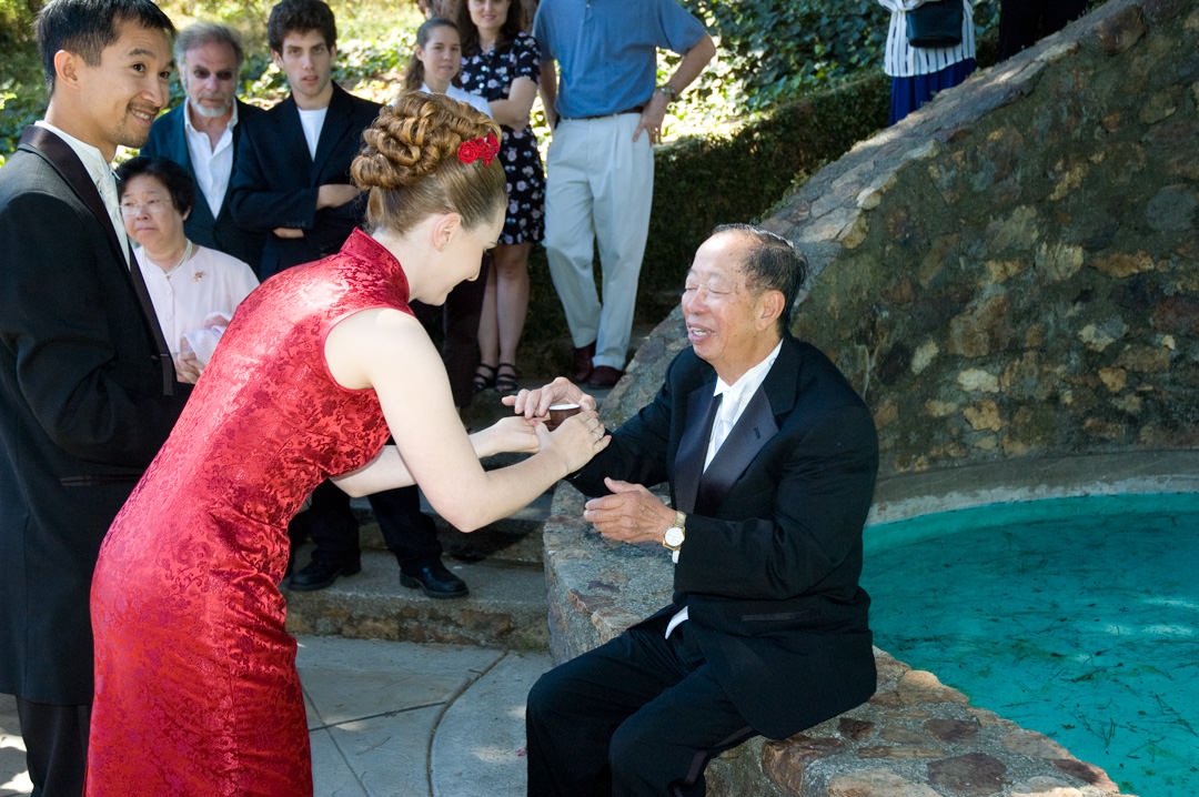 Bride extends tea to father for Chinese tea ceremony