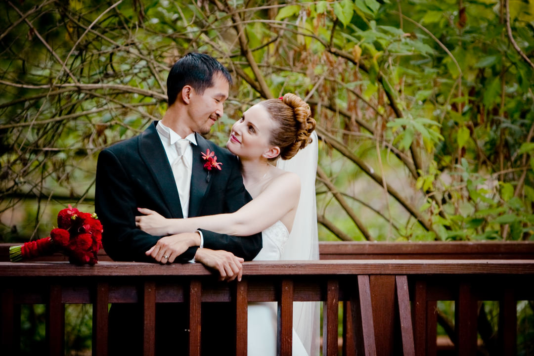 Bride and groom pose on bridge