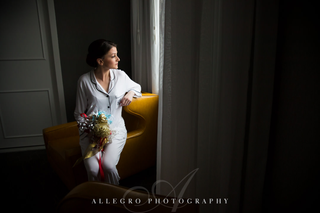 Bride stares out hotel window