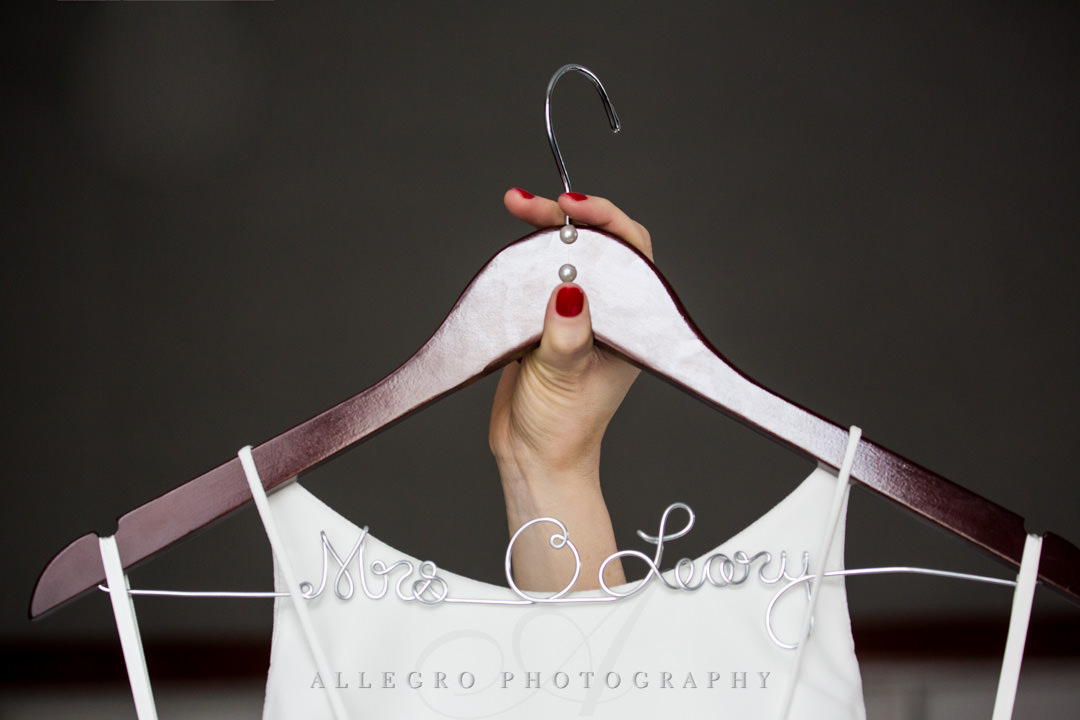 "Bride holds up her wedding dress hanger that says ""Mrs O'Leary"""