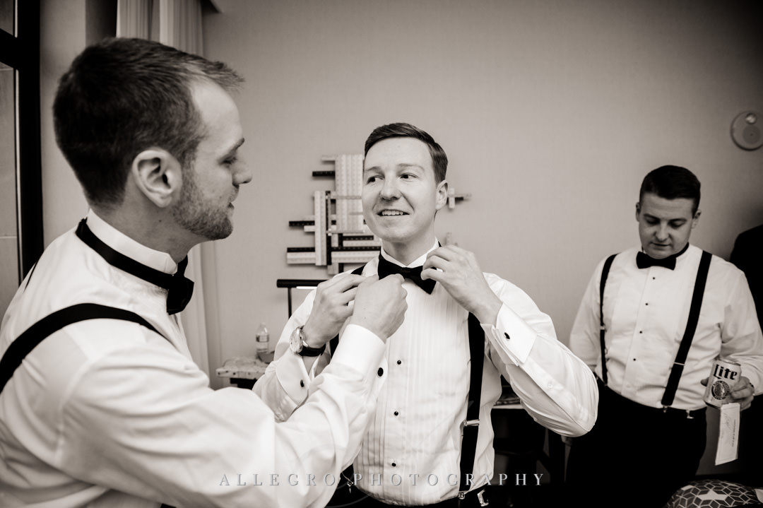 Best man helps groom with his bowtie