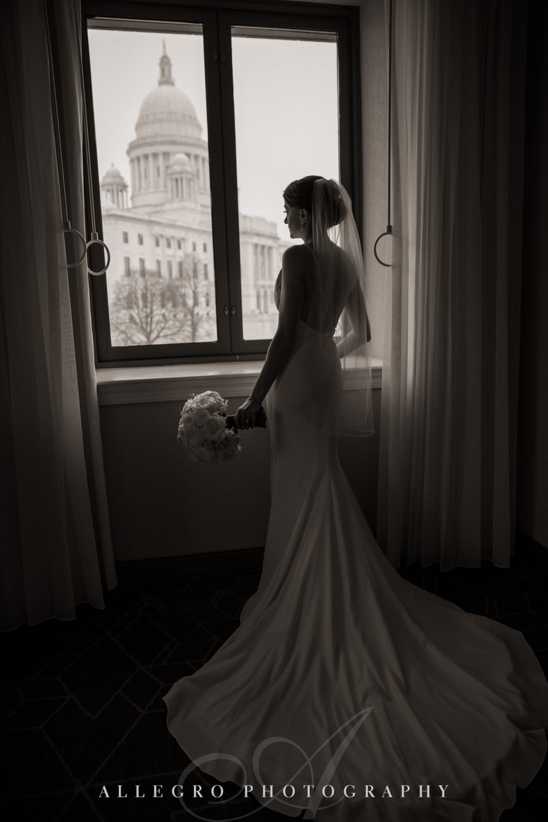 Bride looks outside in her wedding dress- providence state house