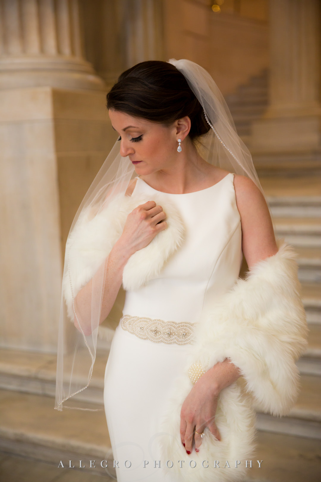 Bride poses with her fur throw in Mikaella bridal gown