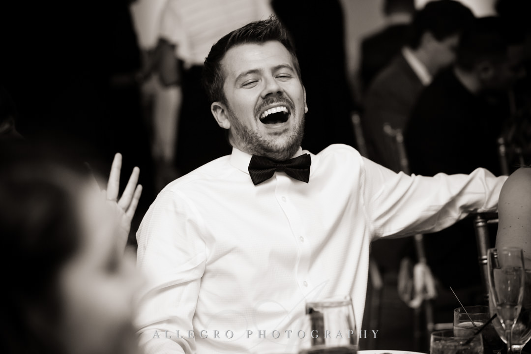 Groomsman laughs at wedding toast
