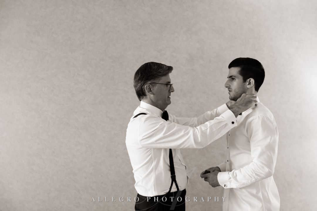 Groom's father helps groom with collar