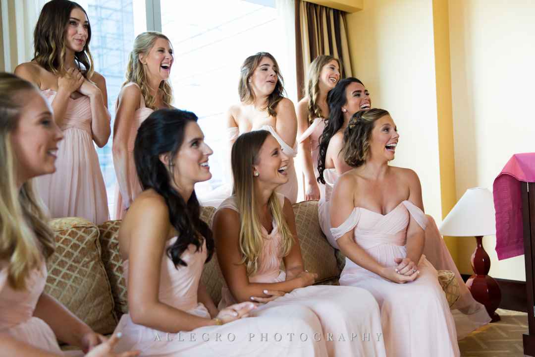 Bridesmaids smile at seeing the bride all ready