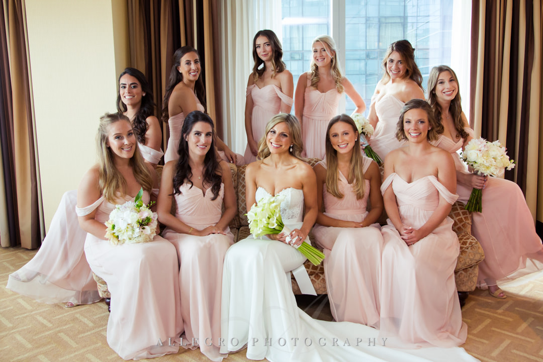 Bridesmaids pose with bride in hotel