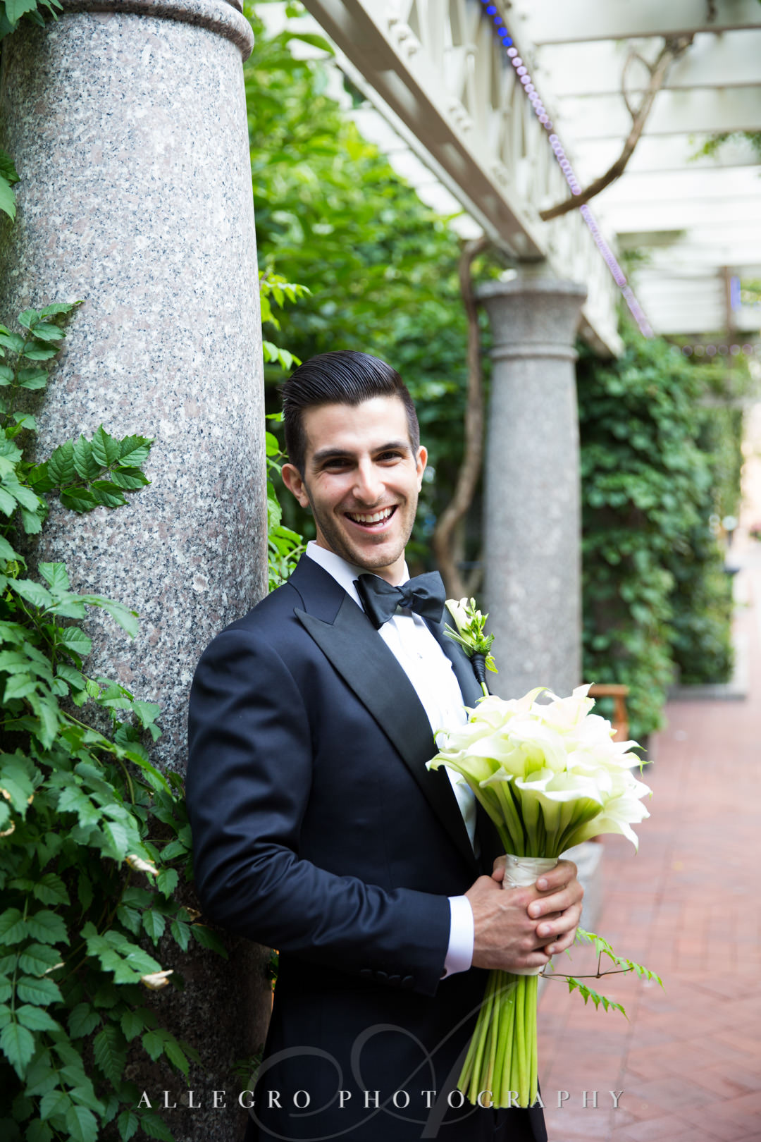 Groom poses with bouquet