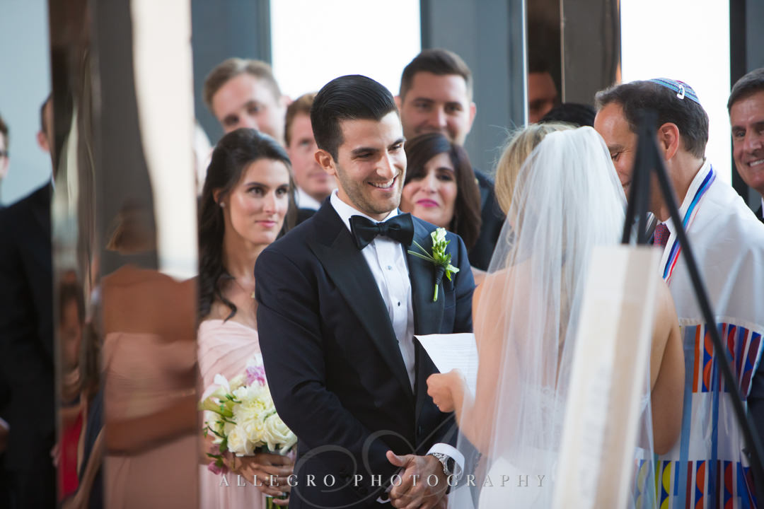 Groom smiles at bride at alter