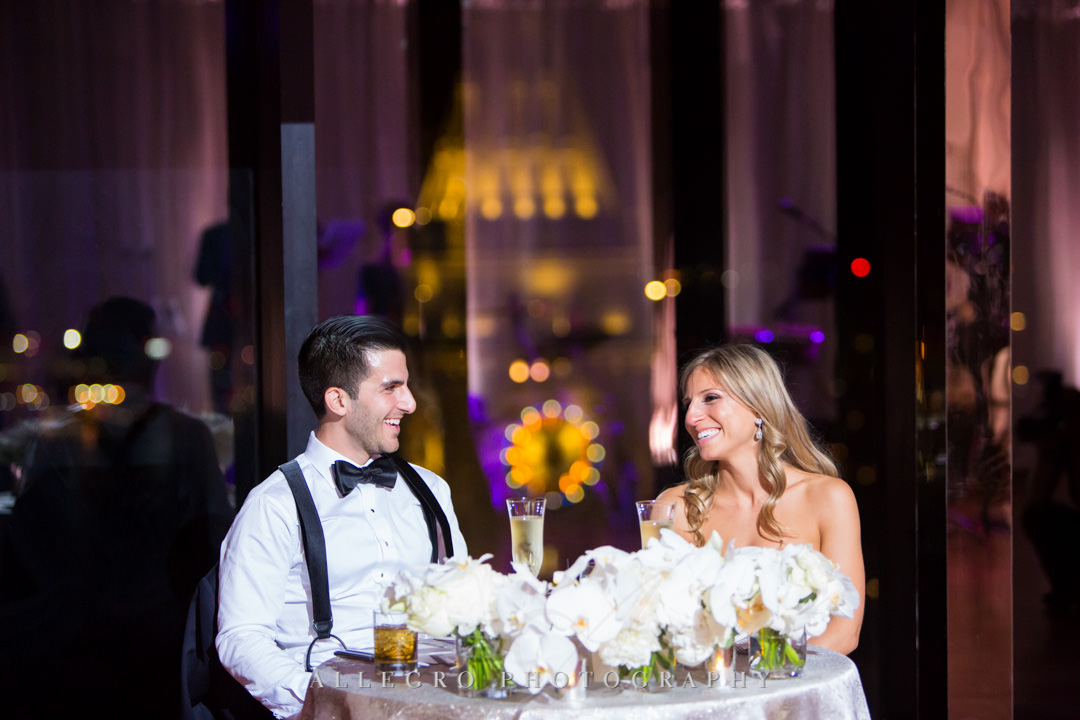 Bride and groom sit at wedding table
