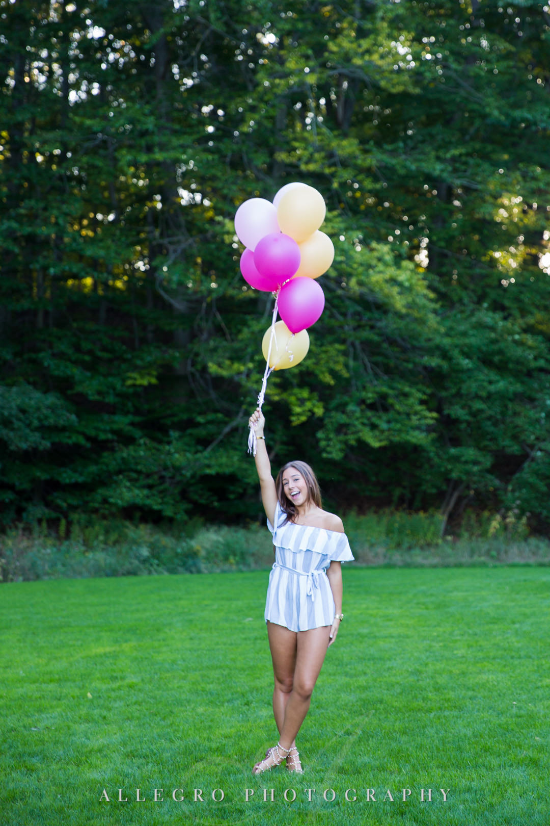 Playful senior in high school holding up balloons at Wellesley College