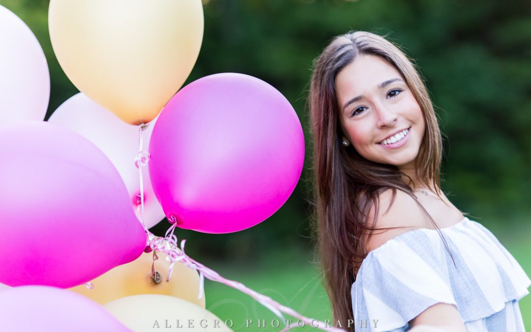 Brunette senior girl posing with balloons