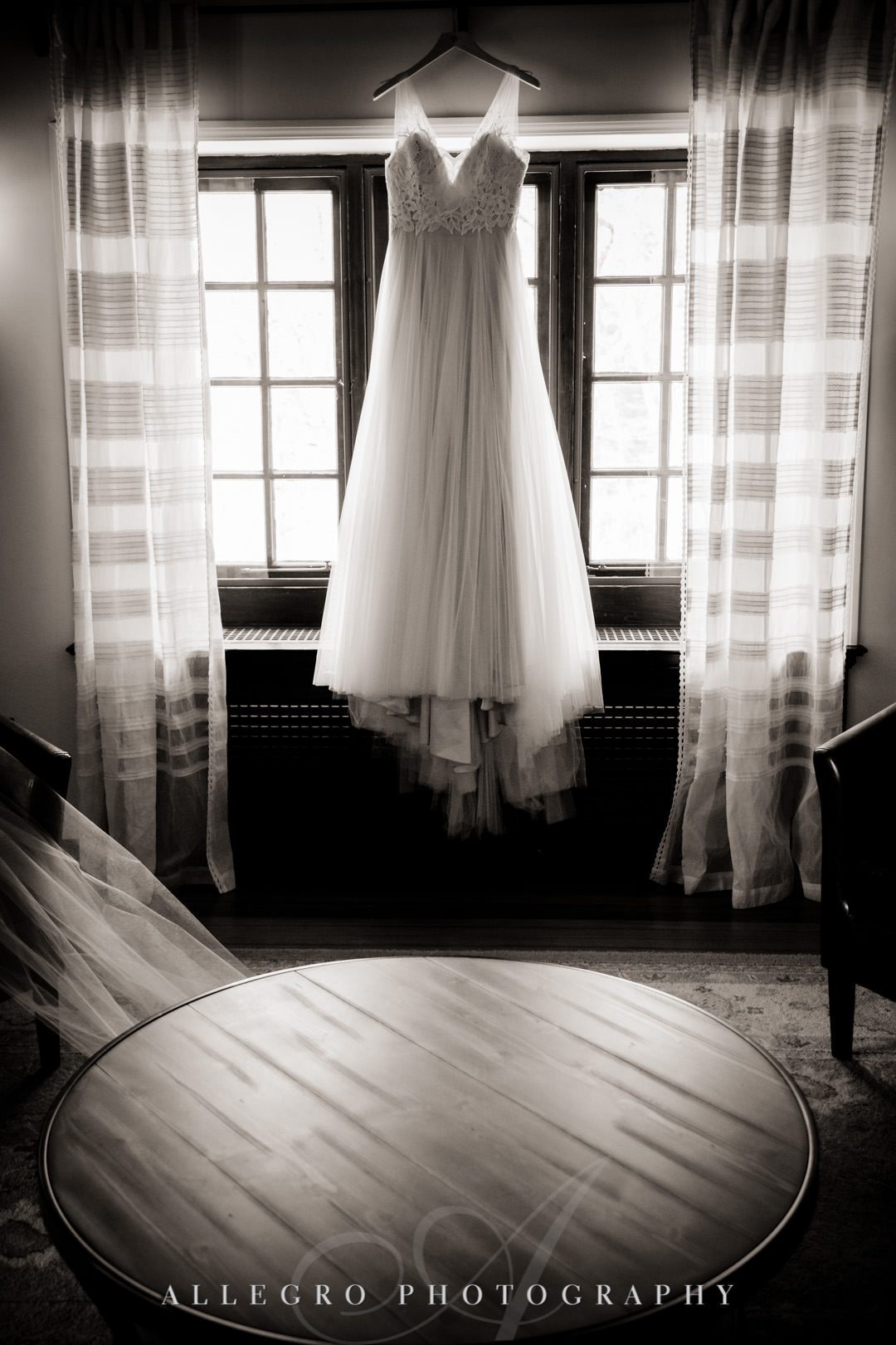 Black and white photo of wedding dress hanging in sunlit room.