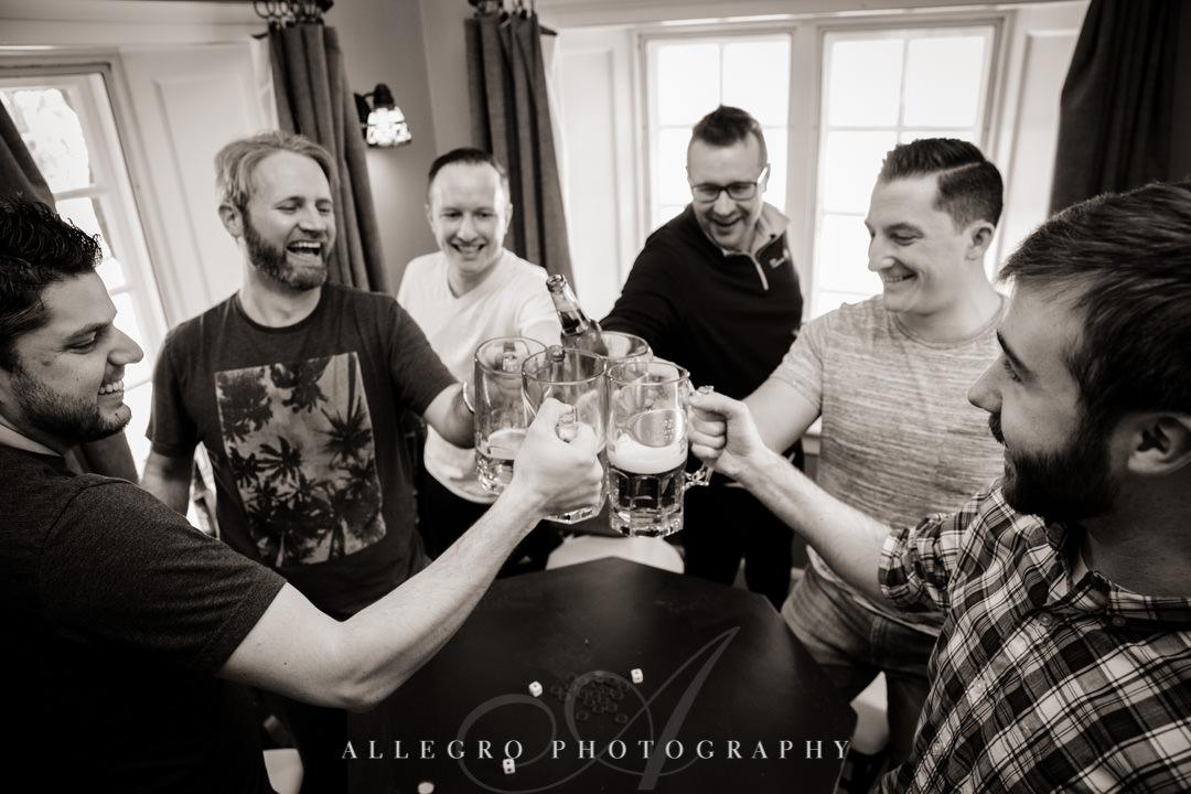 Group of adult men clink beer glasses