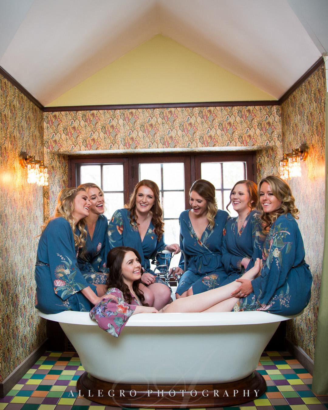 Bridesmaids sit around bride on bathtub in their robes