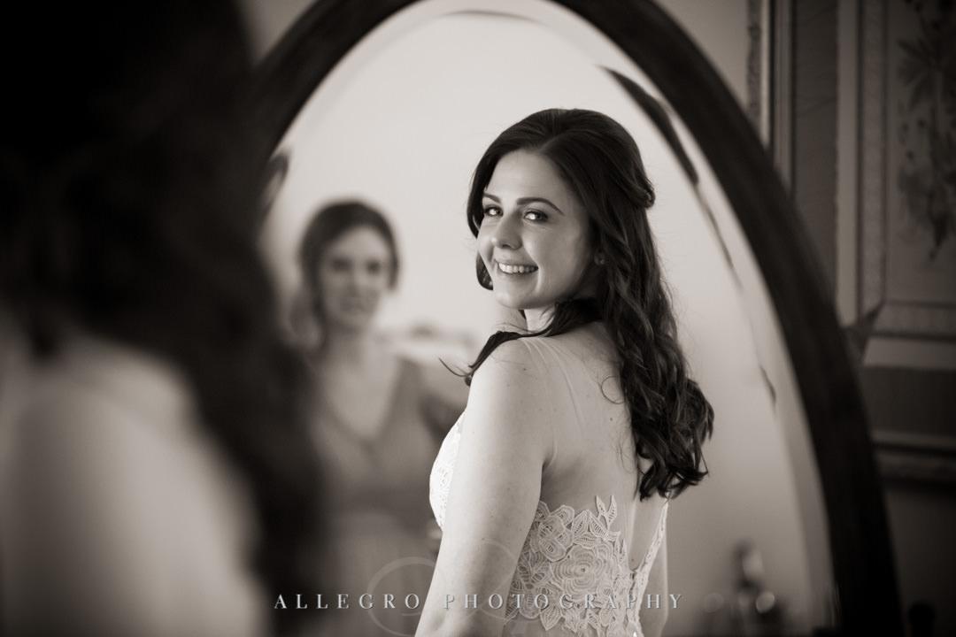 Bride smiles into mirror wearing her wedding dress