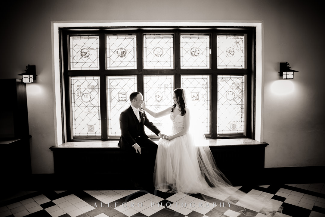 Bride and groom pose for black and white wedding portrait