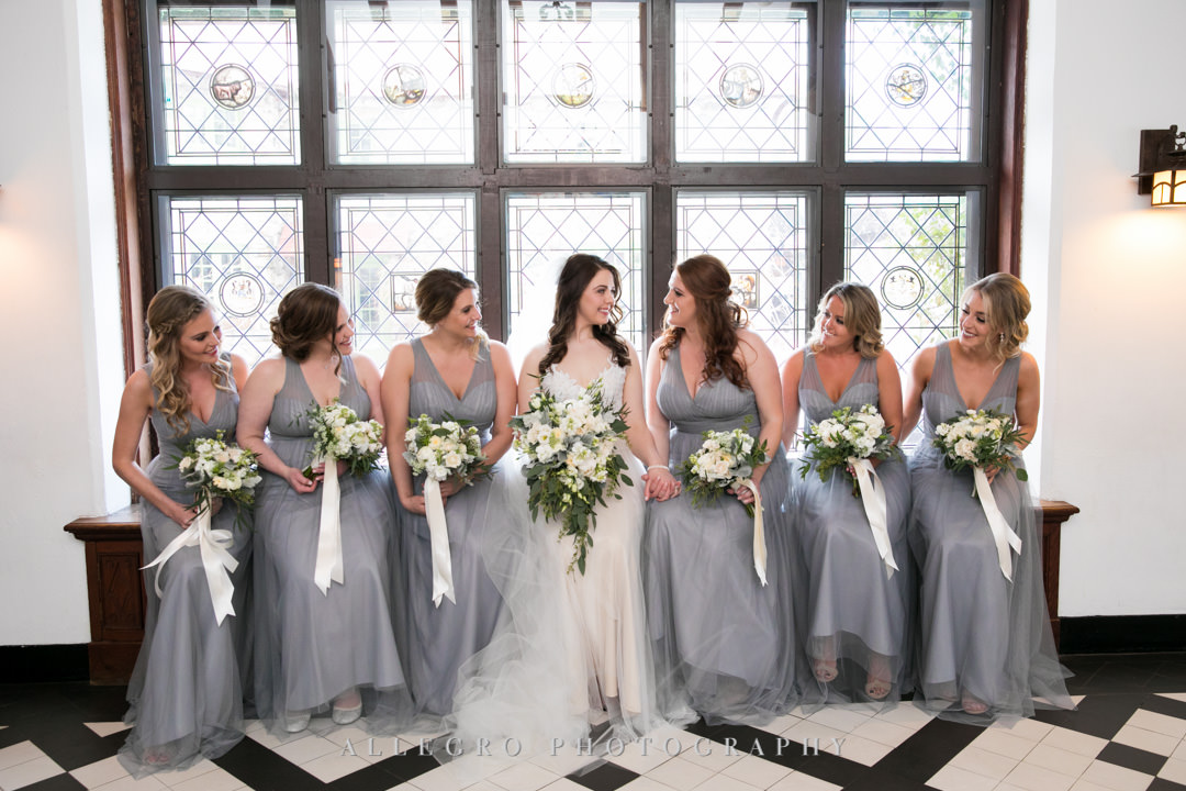 Bride sits with her bridesmaids along a windowsill