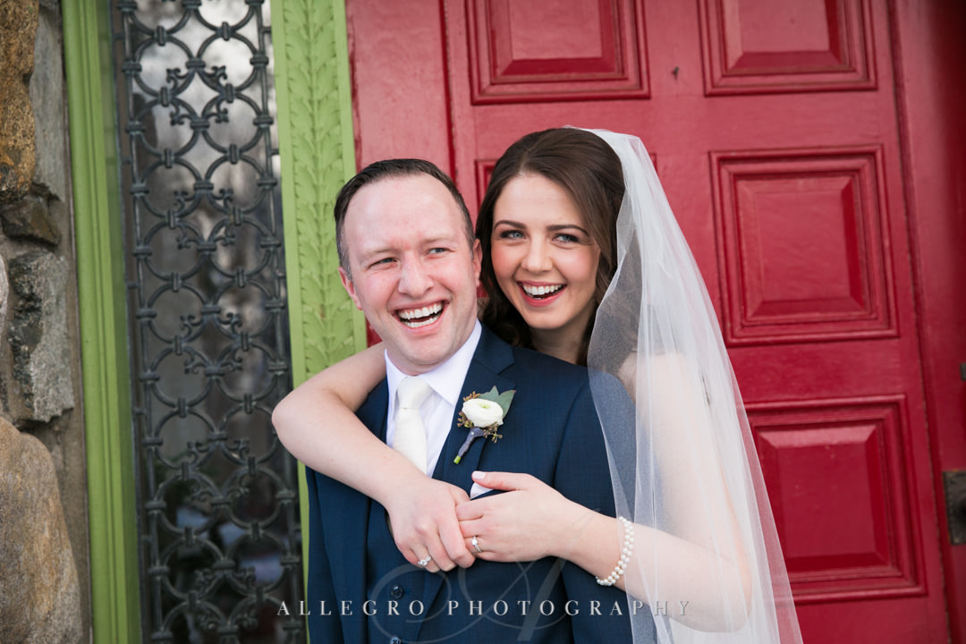 Bride and groom smile in front of bright red door