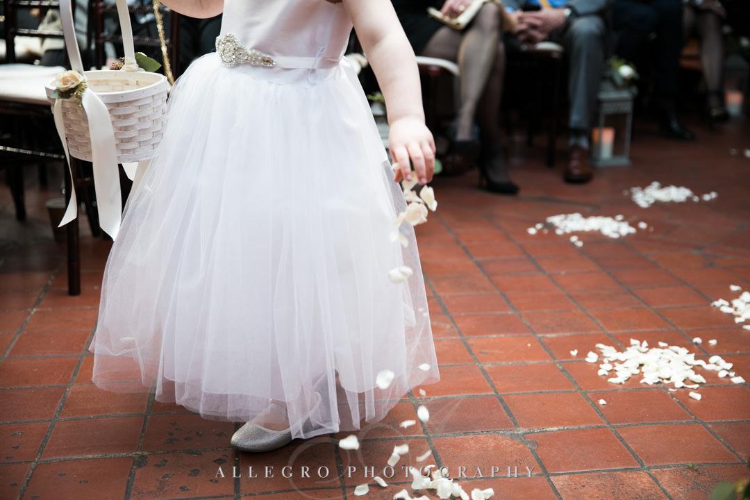 Flower girl sprinkles petals down the aisle