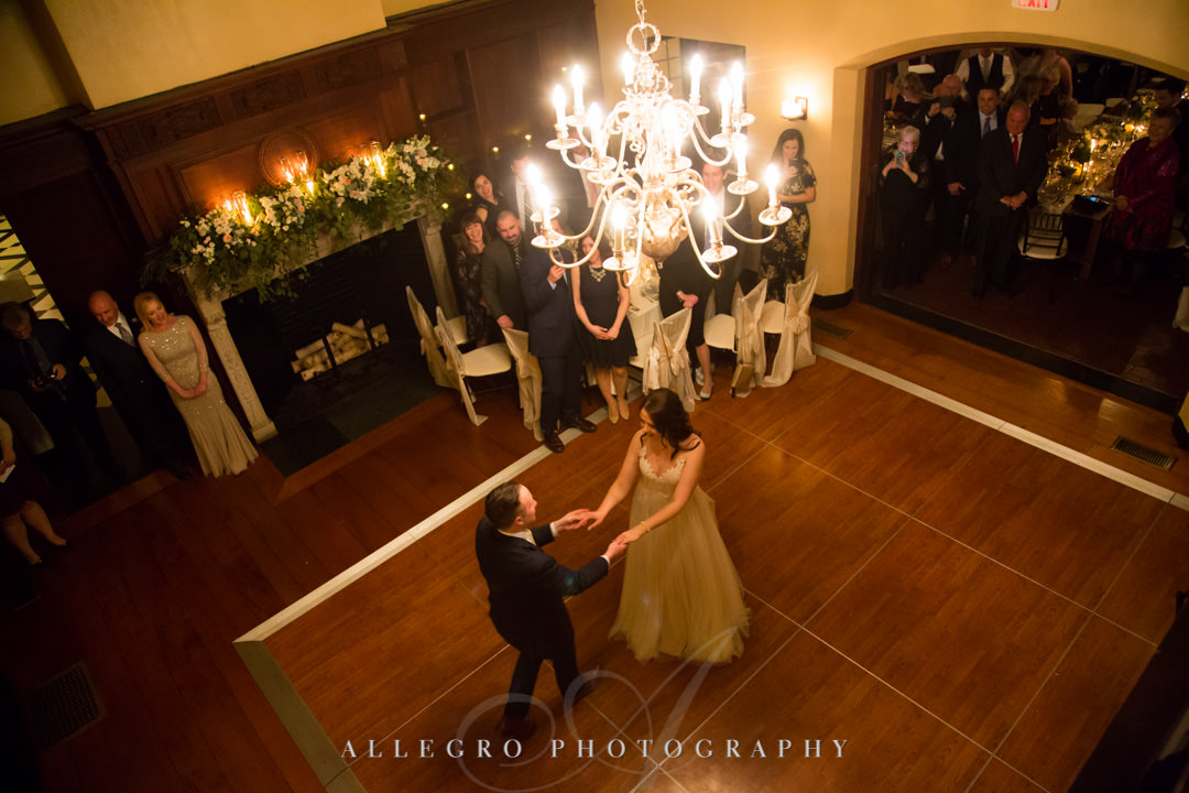 Bride and groom dance under chandelier at wedding reception