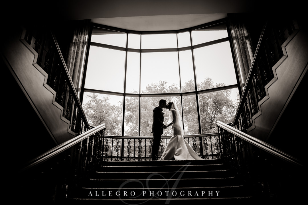 Black and white photo of newlyweds kissing atop a staircase | Allegro Photography