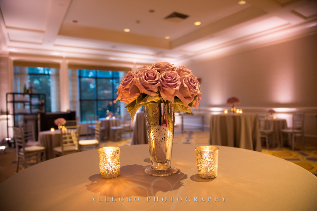 Pastel pink flowers next to two candles | Allegro Photography