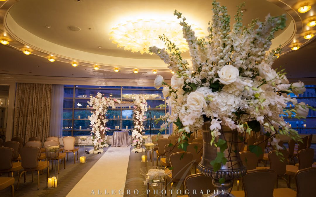 Wedding aisle adorned with flowers on wooden arch | Allegro Photography