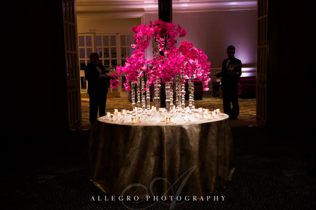 Neon pink flower arrangement surrounded by candles | Allegro Photography