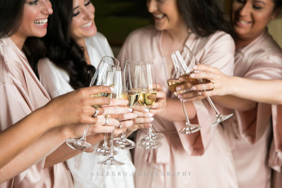 bride and bridesmaids cheers with champagne