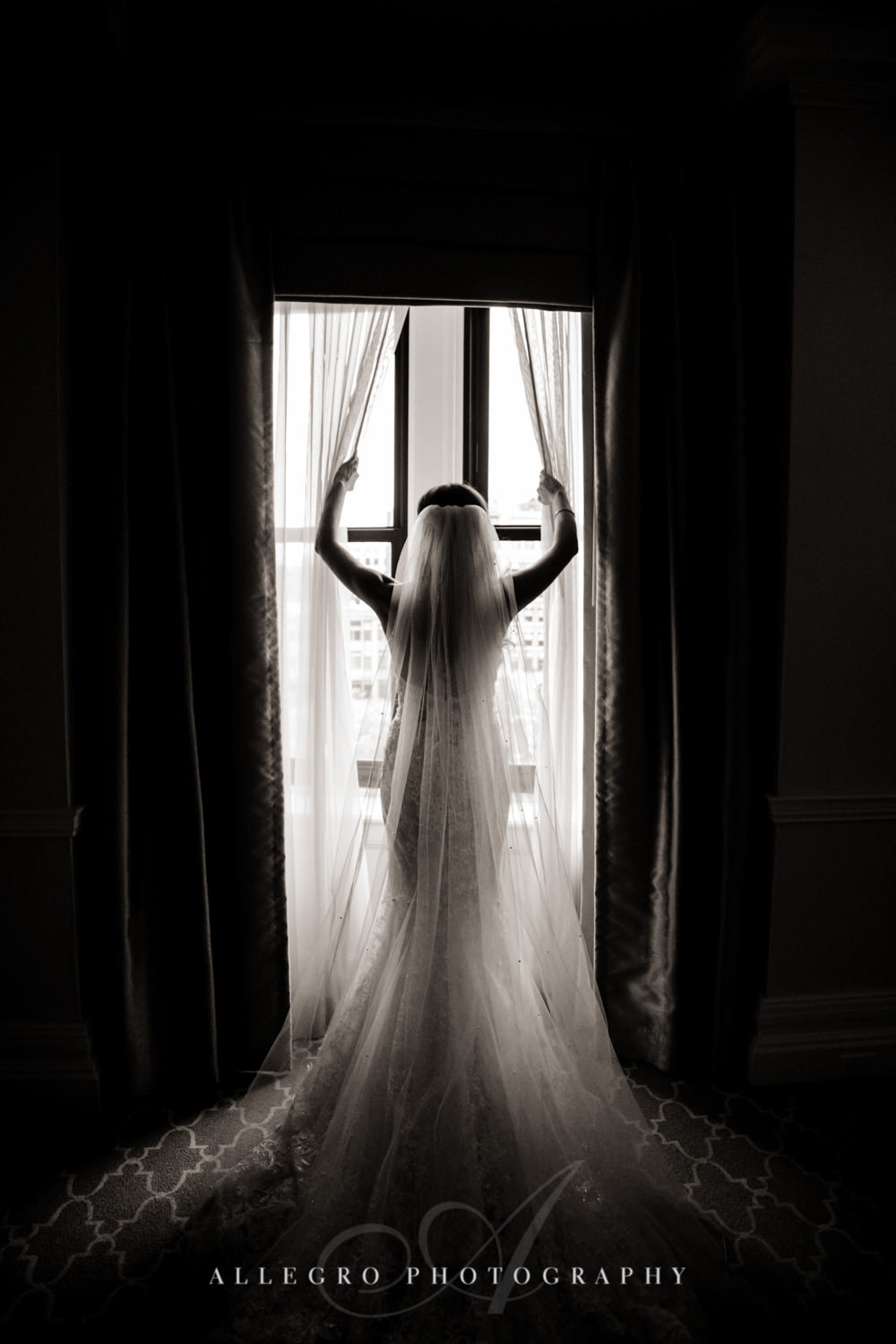 bride opens curtains while wearing wedding dress
