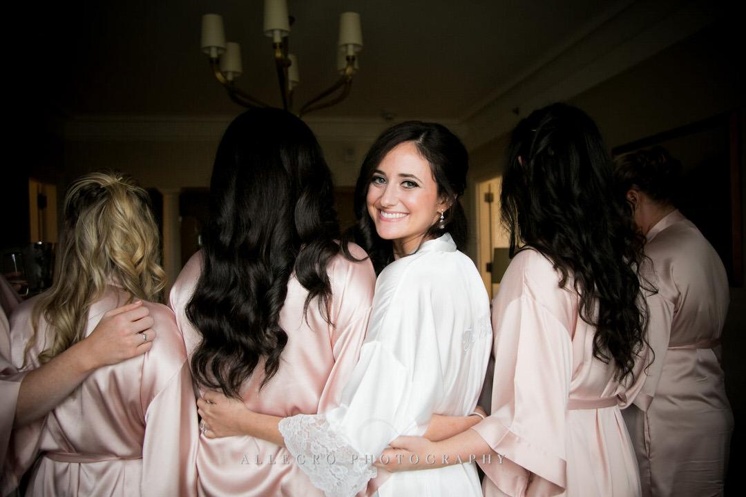 bride smiles as she hugs her bridesmaids