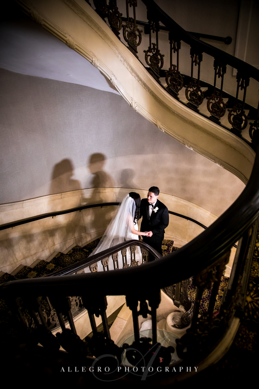 bride and groom hold hands while on the stairs