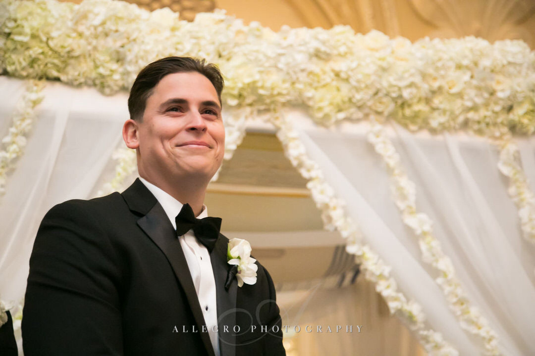 groom smiles as he watches for the bride