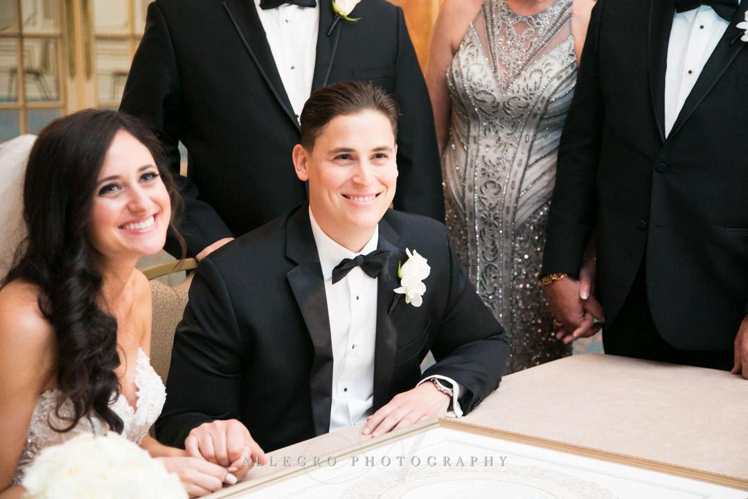 bride and groom smile as ketubah gets signed