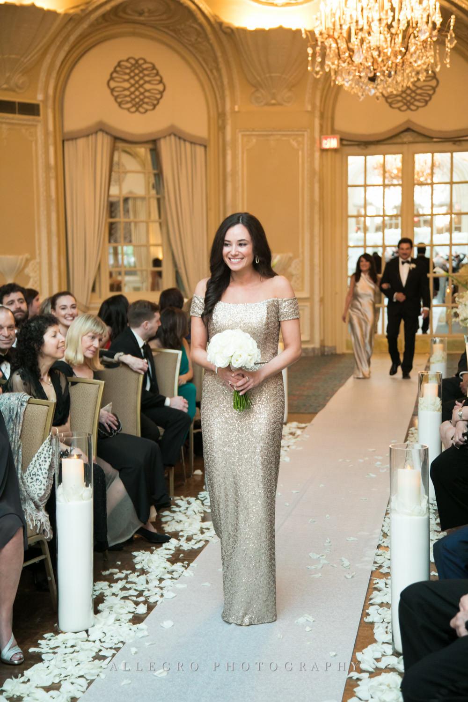 bridesmaid smiles as she walks down the aisle