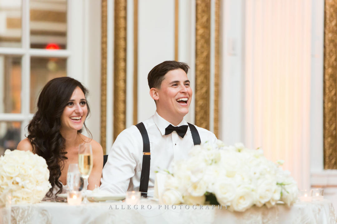 bride and groom laugh while they receive toasts