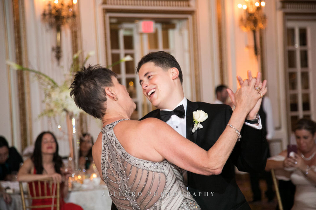 groom smiles as he dances with his mother
